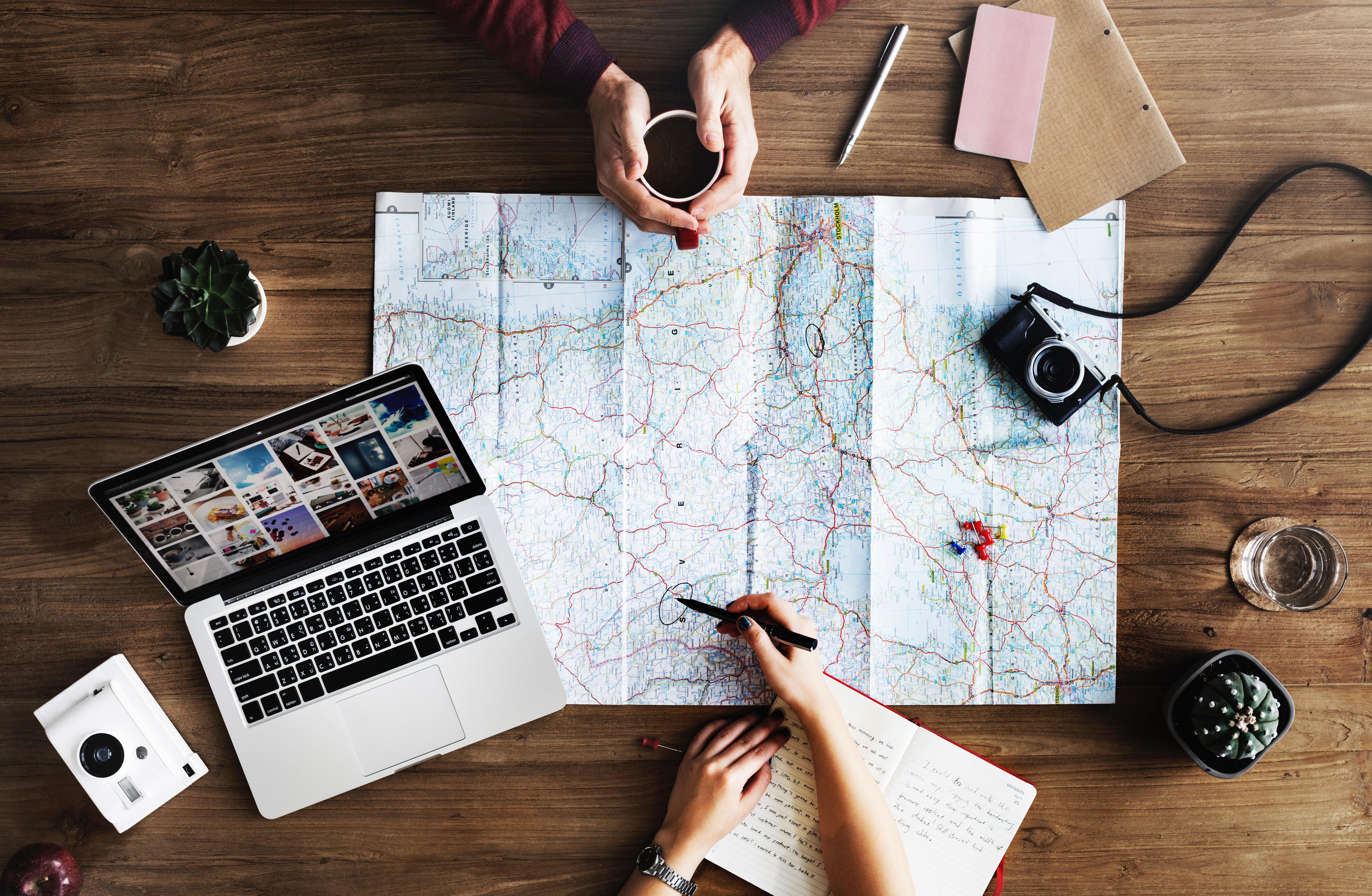 Händer, karta, dator, och anteckningsbok